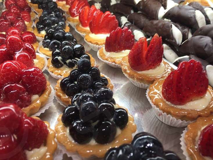 raspberry and blueberry tarts near glazed pastries photo