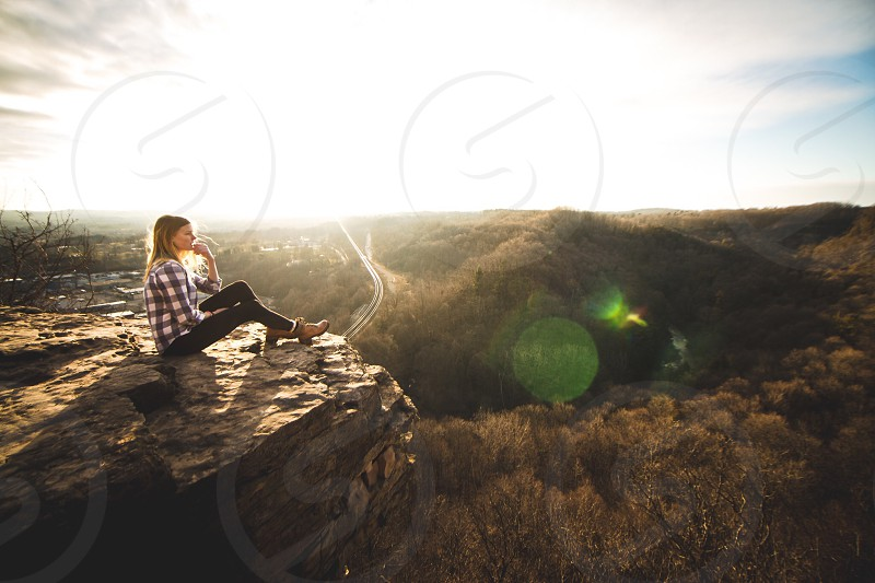 woman in black and white checked long sleeve shirt and black pants sitting on brown rock photo