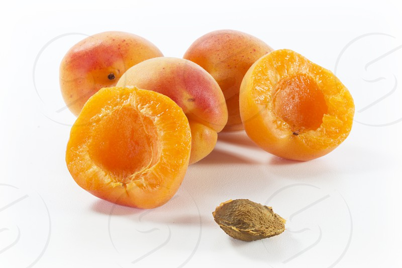 three whole apricots and two apricot halves with the stone out. orange; fruit; fresh fruit;  photo