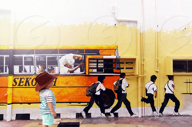 painting of a boy watching group of boys running from yellow bus photo
