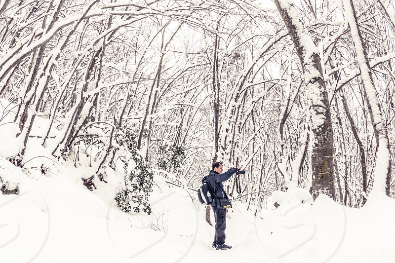 Man With A DSLR Camera In A Snowy Forest Landscape With Trees photo