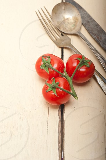 ripe cherry tomatoes cluster over white rustic wood table photo