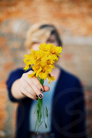 woman holding yellow flower photo