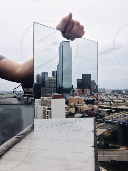 white high rise building reflection on mirror photo