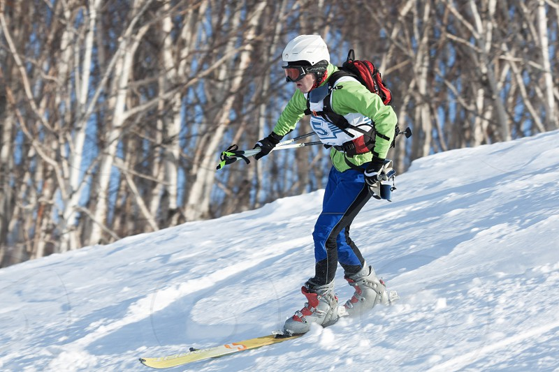 KRASNAYA SOPKA PETROPAVLOVSK-KAMCHATSKY KAMCHATKA RUSSIA - FEB 4 2012: Ski mountaineer rides skiing on mountain on forest background. Ski-mountaineering competitions - Cup Petropavlovsk City. photo