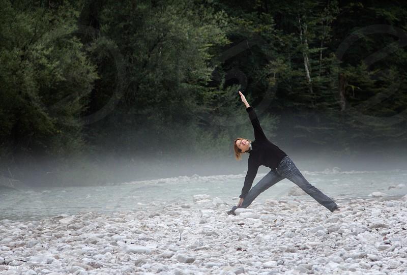 A woman practices a yoga stretch on a rocky river shore on a misty morning near Lake Bohinj Slovenia photo