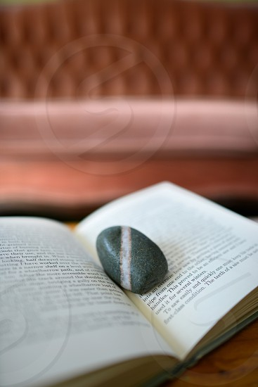 An open book with a stone on it. photo