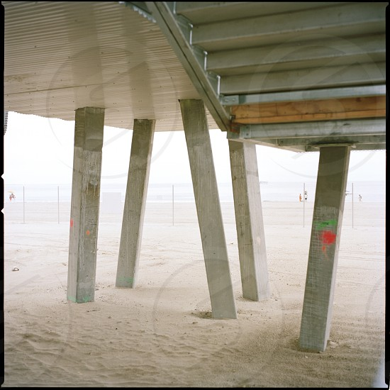 gray wooden posts on white sand photo