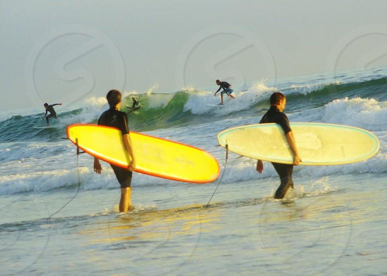 2 man holding a surfboard o photo