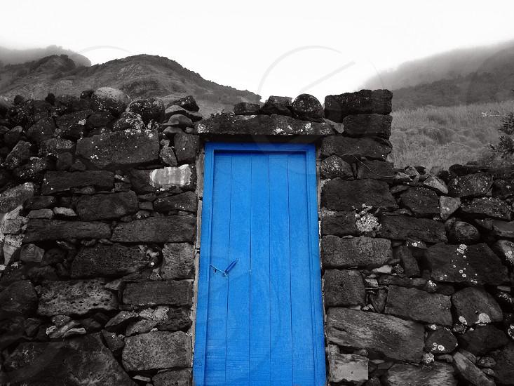 selective color photography of blue wooden door between concrete wall photo