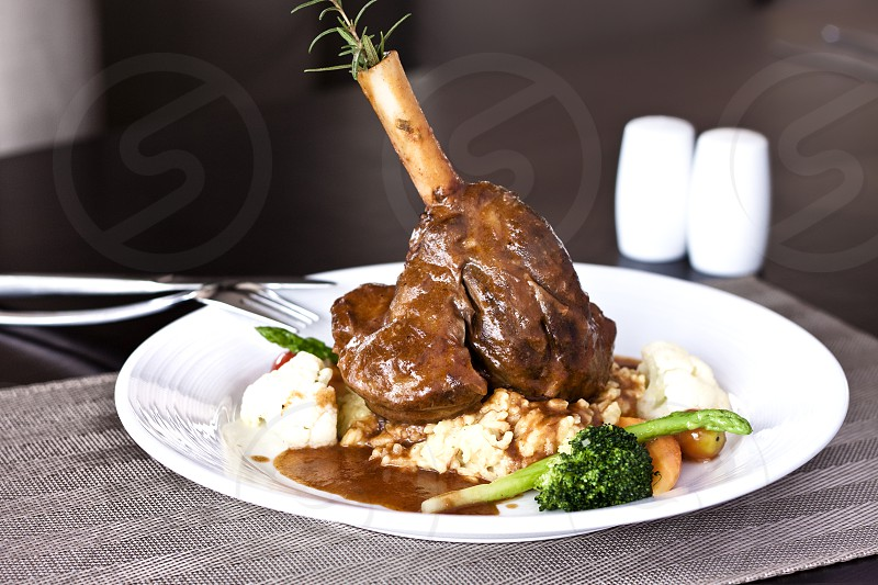 Delicious lamb shank with creamy risotto and vegetables photo