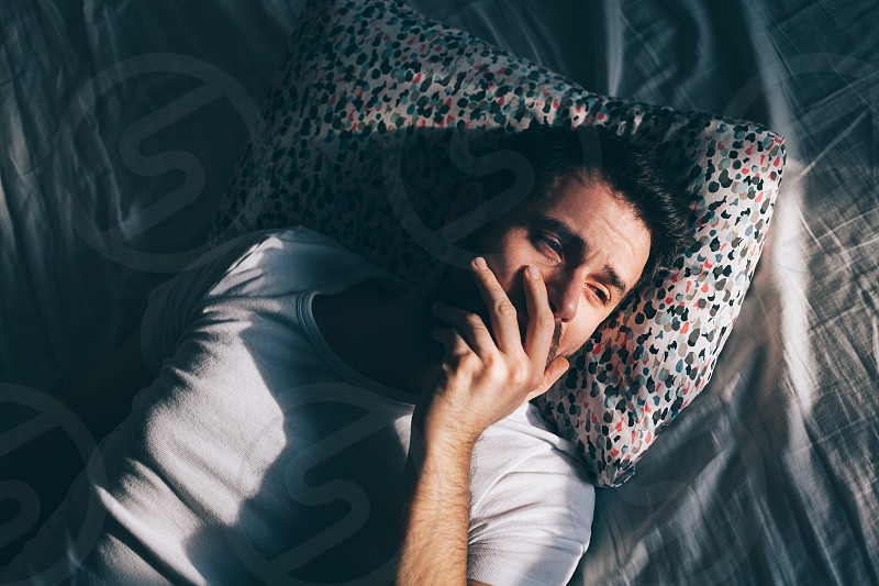Young depressed man crying in bed photo