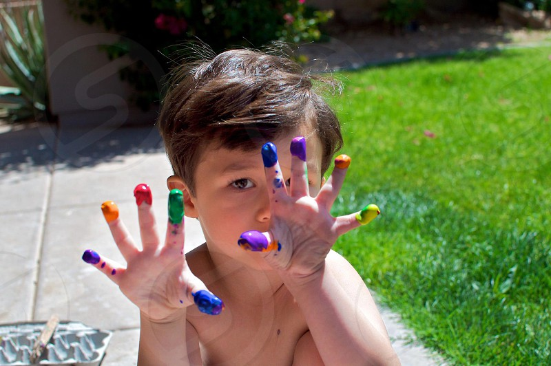 Young boy outwide enjoying his finger paints and showing his messy hands.  photo
