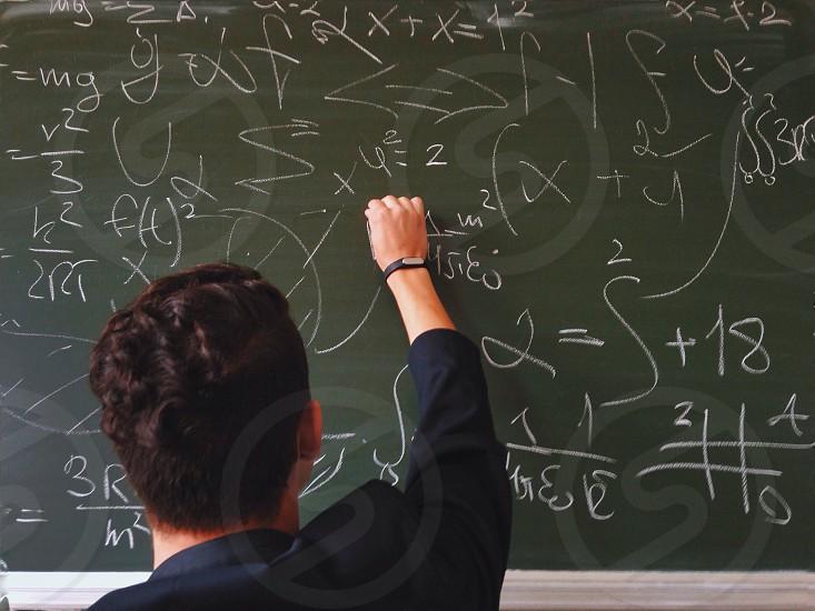 man in blue dress shirt writing on chalk board photo