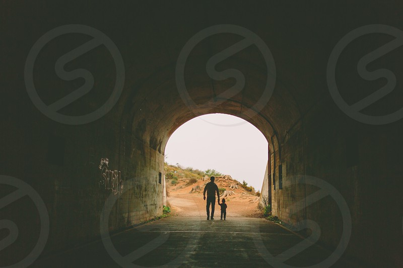A father and son walking together through a tunnel framed in silhouette.  photo