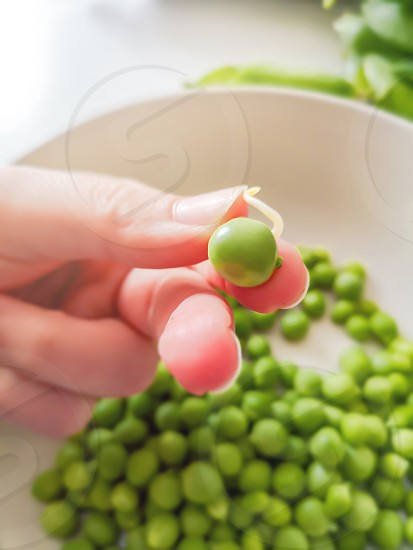 Woman's fingers holding green pea. Healthy food and lifestyle photo
