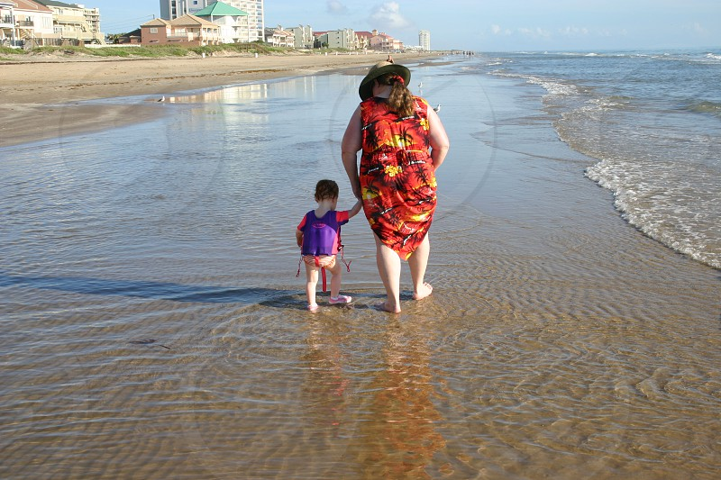 Grandmother and young grand daughter walking hand in hand in the surf on a sunny beach on Padre Island in the Gulf Coast of Texas photo