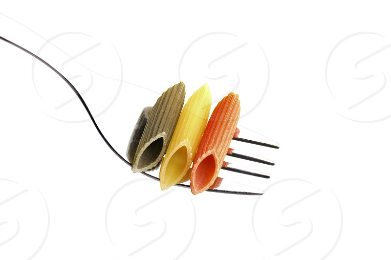 italian penne pasta on a fork on white background photo