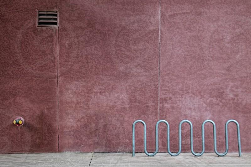 Empty bike rack on a city street near a pink wall photo