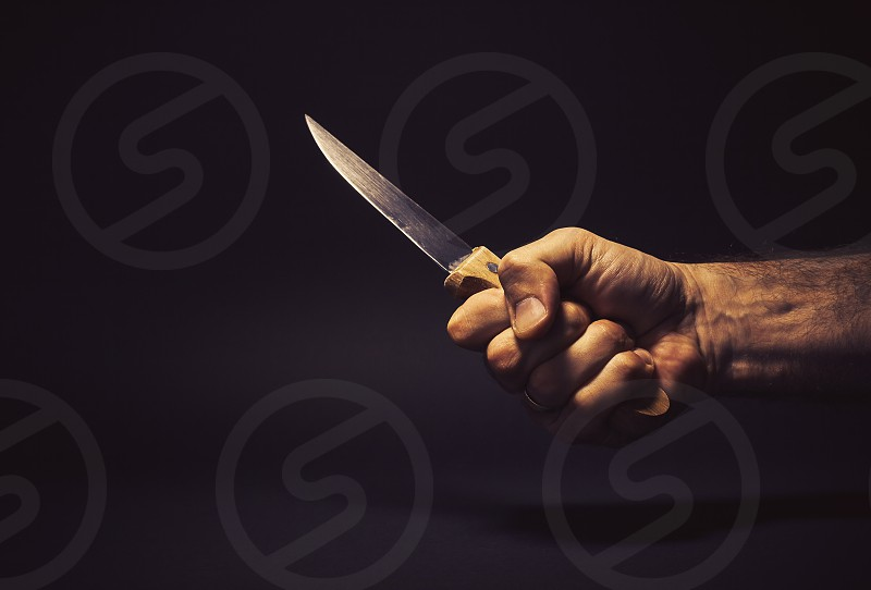 Conceptual composition man's hand holding a big kitchen knife as self defense   weapon or some kind of horror scene.  photo