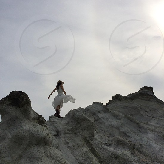 woman standing on rock wearing a white dress photo