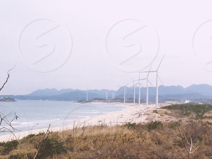white wind turbine on seashore photo