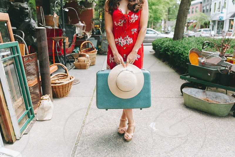 A stylishly dressed woman holding a suitcase and hat.  photo