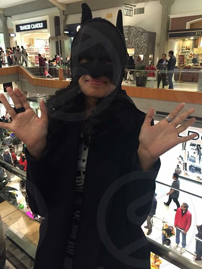 person wearing batman mask costume near action figures photo