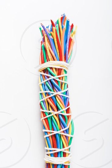 Bundle of colorful electronic wires wrapped light a bundle of sage against a white background. photo