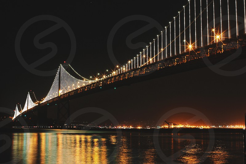 black suspension bridge with lights on over water at night photo