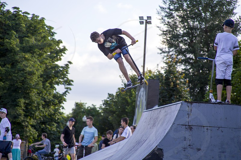 A boy skates on a ramp in a  on the summer day photo