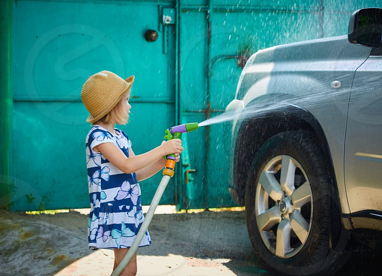 Little girl helps wash the car photo