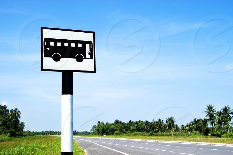 Bus stop signpost in non urban scene photo