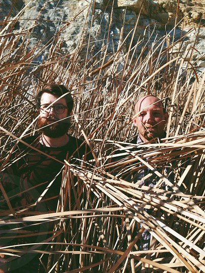 two men standing at dried grass photo