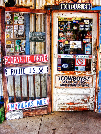 Route 66 and colorful signs cover the door to a small grocery store photo