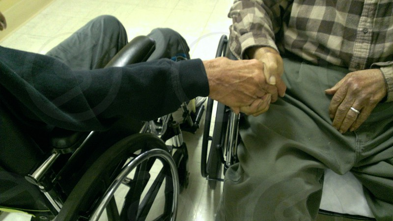 2 people sitting on wheelchairs shaking hands photo