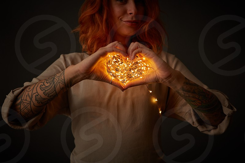 garland in the shape of a heart girl holding in hands In the dark photo
