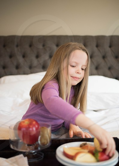girl kid eating healthy fruit breakfast hotel hotel room travel family vacation holiday fun breakfast in bed food photo