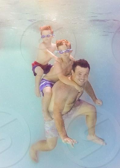 Dad and sons underwater swim photo