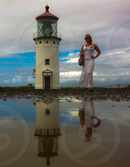 The curves of a woman contrast the straight lines of a lighthouse.  photo