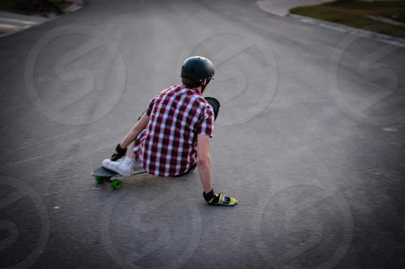man on a skateboard wearing black with white plaid shirt photo