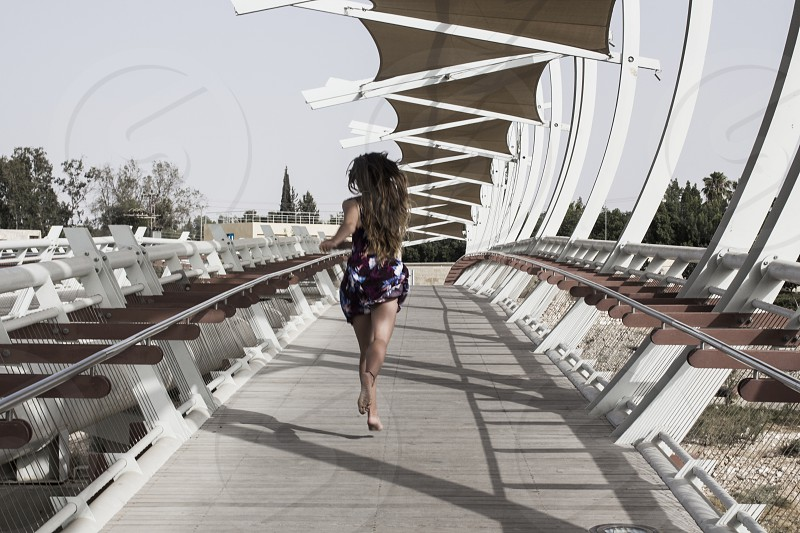woman in maroon and purple mini dress running on grey wooden pathway during daytime photo