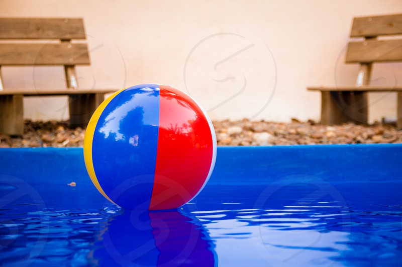 Colorful beach ball floating in pool. photo