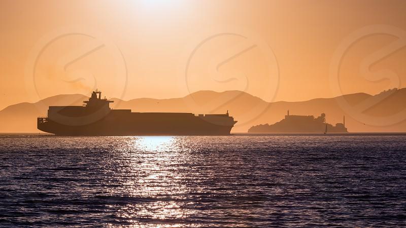 Alcatraz island penitentiary at sunset and merchant ship in san Francisco California USA photo