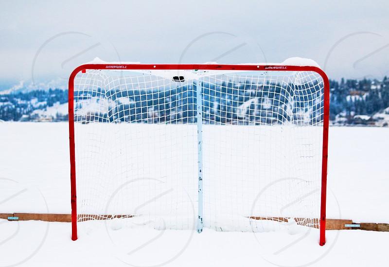 hockey ice hockey frozen lake hockey net puck mountains photo
