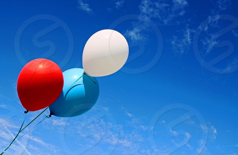A red a white and a blue helium balloons extend from the left corner of the against against a blue sky. photo