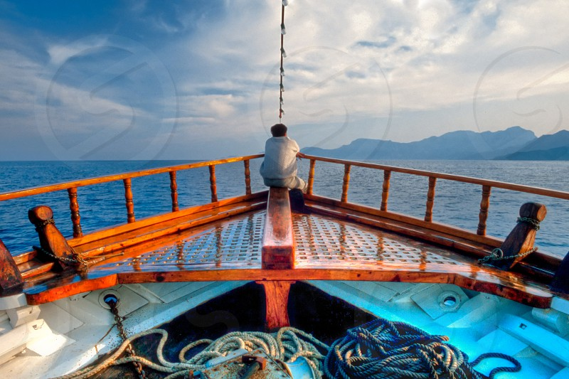 Man day-dreaming at the bow of traditional Greek vessel cruising the aegean sea photo