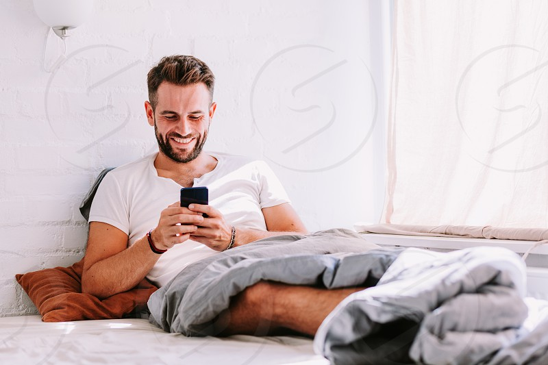 Young man using smartphone in the bed in the morning photo
