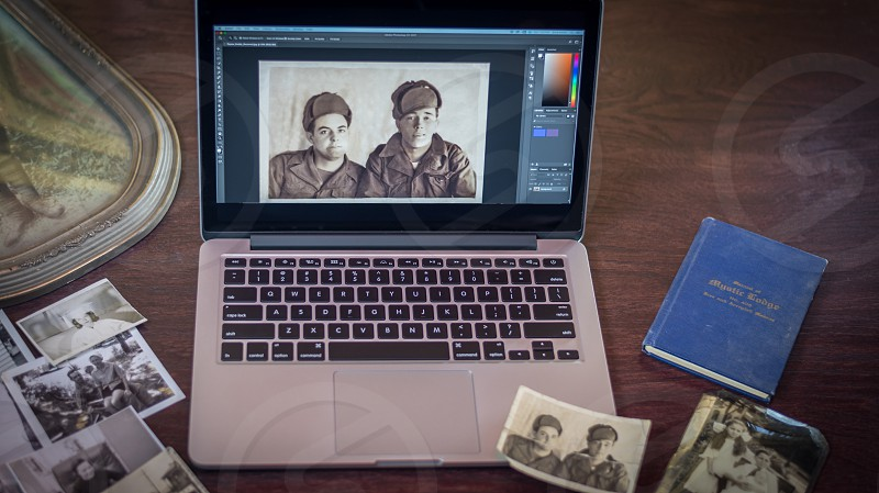 Laptop and old photos laying on a table with digital version on computer monitor. photo