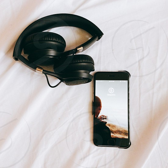 man holding phone wallpaper of space gray iphone 6 beside black wireless headphones on white textile photo